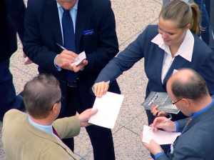 Business Learning - How to Get Customers With Seminars, Speaking, and Word-of-Mouth - Business People Handing Papers to Each Other